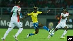 Le Gabonais, Didier Ibrahim Ndong, centre, tente un drible face à Jonathan Zongo du Burkina Faso, à droite, lors du match de la Coupe d'Afrique des Nations entre le Burkina Faso et le Gabon à Bata, Guinée équatoriale, 17 janvier 2015.