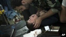 Ozod Suriya armiyasi jangchisi Halabdagi to'qnashuvda jarohat olgan bolani ovutmoqda. 11-oktabr.