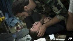 ທະຫານກອງທັບຊີເຣຍເສລີກໍາລັງໃຫ້ການປິ່ນປົວເດັກນ້ອຍ ທີ່ຖືກລະເບີດ ຢູ່ເມືອງ Aleppo, Syria.