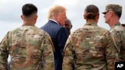 President Donald Trump greets member of the military as he arrives on Air Force One at Wheeler-Sack Army Air Field in Fort Drum, N.Y.