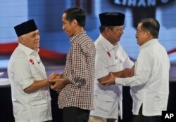 Indonesian Presidential candidates Joko Widodo, second left, his running mate Jusuf Kalla, right, Prabowo Subianto, second right and his running mate Hatta Rajasa, left, congratulate each other during a televised debate in Jakarta, Indonesia, Saturday, Ju