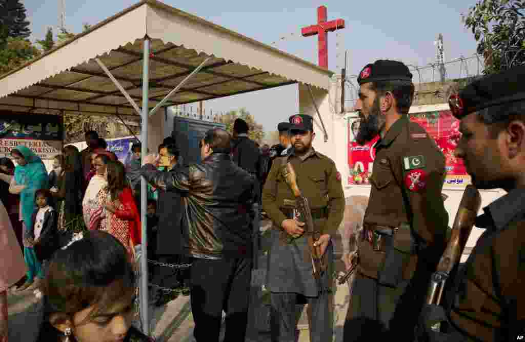 Pakistani paramilitary officers and policemen are on alert as Pakistani Christians leave a church after attending the Christmas mass at a church in Islamabad, Dec. 25, 2016.