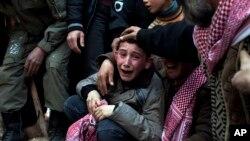 지난 2012년 3월 시리아 이들립에서 내전사태로 아버지를 잃은 아들이 오열하고 있다.