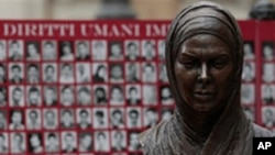 Bust of Iranian Protest Victim Neda Agha Soltan , a student killed during election protests in Tehran in 2009, is seen in front of a banner showing pictures of what Iranian opposition groups say are victims of the Iranian regime.