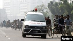 FILE – A traditional ambulance rushes past trishaws on a highway in Gazipur, 50 km (31 miles) from the capital Dhaka, Dec. 4, 2006.