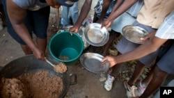 Para siswa memegang piring mereka saat pembagian makan di sebuah sekolah umum di Bombardopolis, Haiti (Foto: dok).