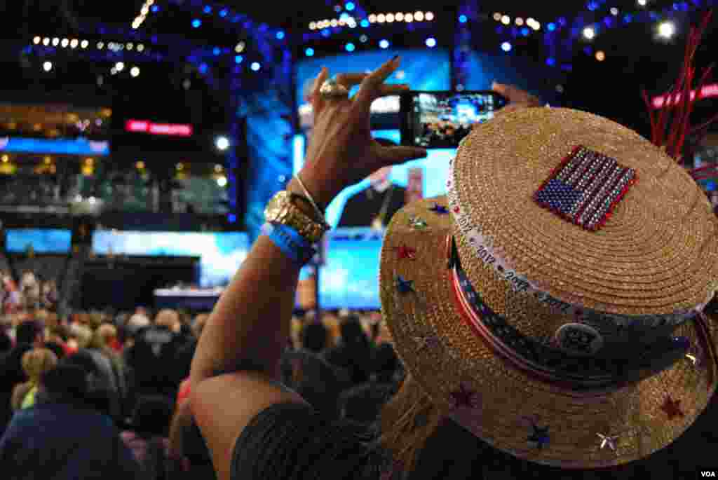 A woman records the invocation at the Democratic National Convention, Charlotte, North Carolina, September 4, 2012. (J. Featherly/VOA)
