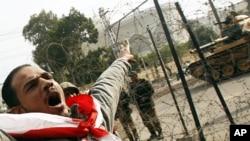 星期五一名反政府示威者在開羅總統府前面的坦克前高呼口號。