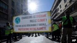 "Para pengunjuk raa memegang spanduk bertuliskan ""Ubah Sistem, bukan iklim, lindungi planet kita"" dalam unjuk rasa untuk perubahan iklim di Marseille, selatan Perancis, 16 Maret 2019."