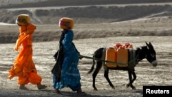 Afghan kochi nomad women carry water containers on their heads as they walk with a donkey outside of Maidan Shar, the capital of Wardak province, Sept. 8, 2013.