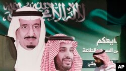 Seorang pria membawa makanannya saat dia berjalan melewati spanduk yang menunjukkan Raja Saudi Salman, kiri, dan Putra Mahkota Mohammed bin Salman, di Jiddah, Arab Saudi, 12 November 2019. (Foto: AP)