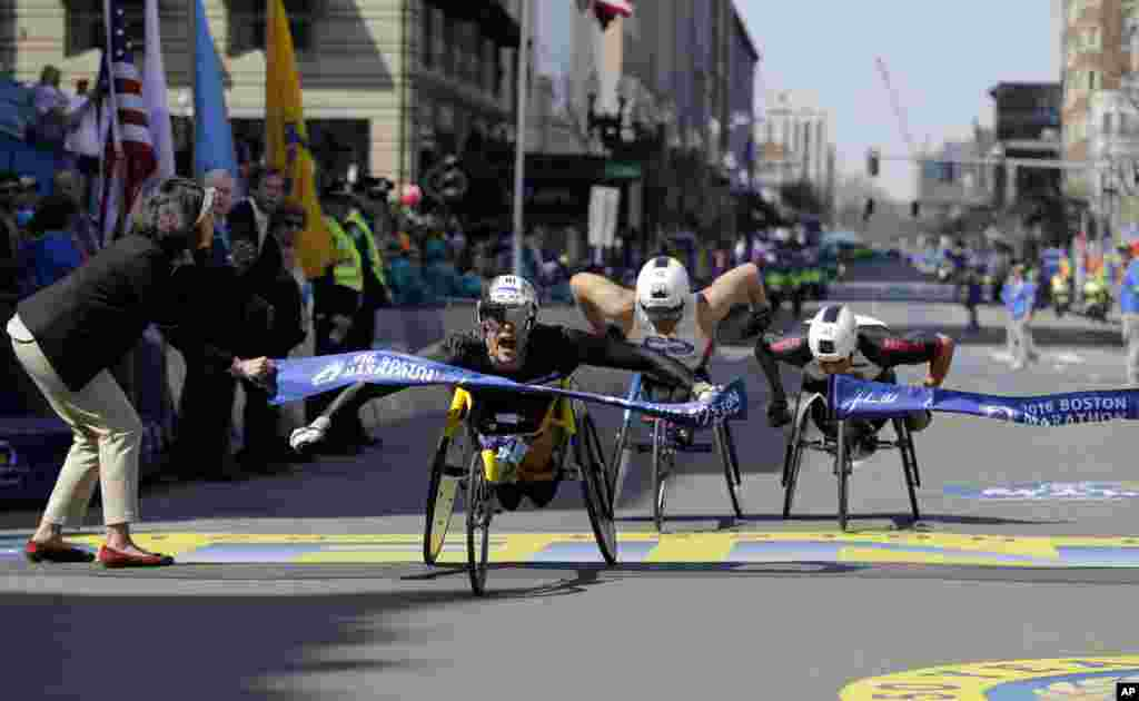 Marcel Hug, of Switzerland, breaks the tape ahead of Kurt Fearnley, of Australia, center, and Ernst Van Dyk, of South Africa, in the wheelchair division of the 120th Boston Marathon in Boston, Massachusetts, USA.