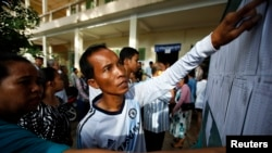 People look through the voters' list after a polling station opened for the general elections in Kandal province July 28, 2013.