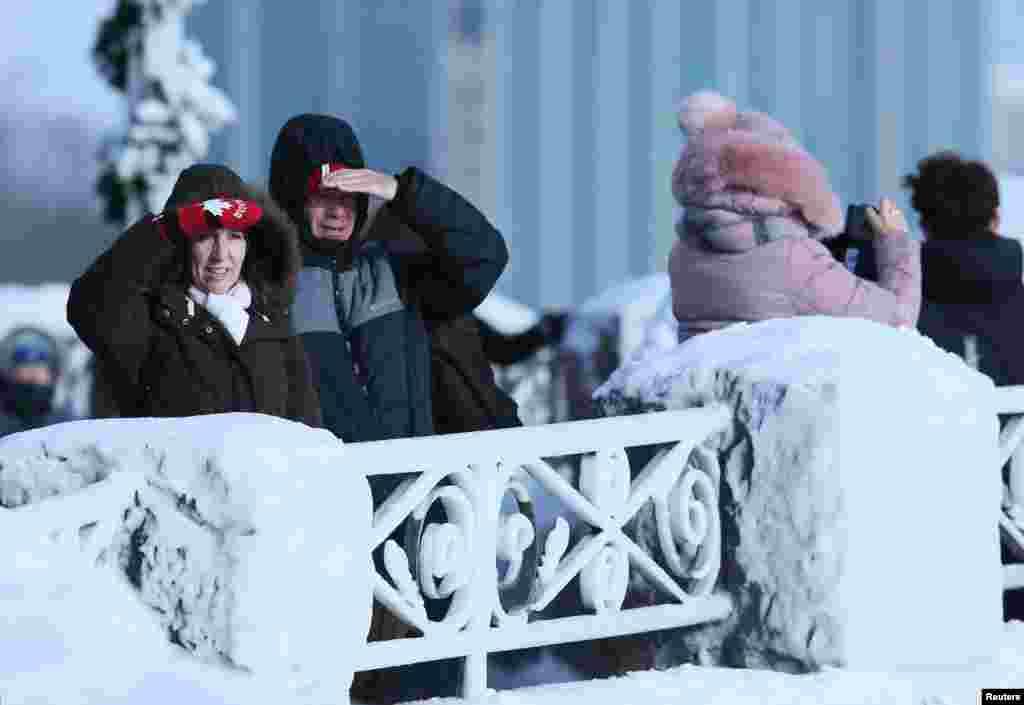 """在尼亚加拉瀑布的岸边,冰雪结成的""""雕栏玉砌""""旁,游客有的观望,有的照相(2018年1月3日)"""