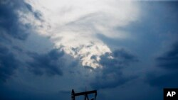 FILE - In this April 21, 2020 file photo, a pumpjack is pictured as a storm moves in Oklahoma City.