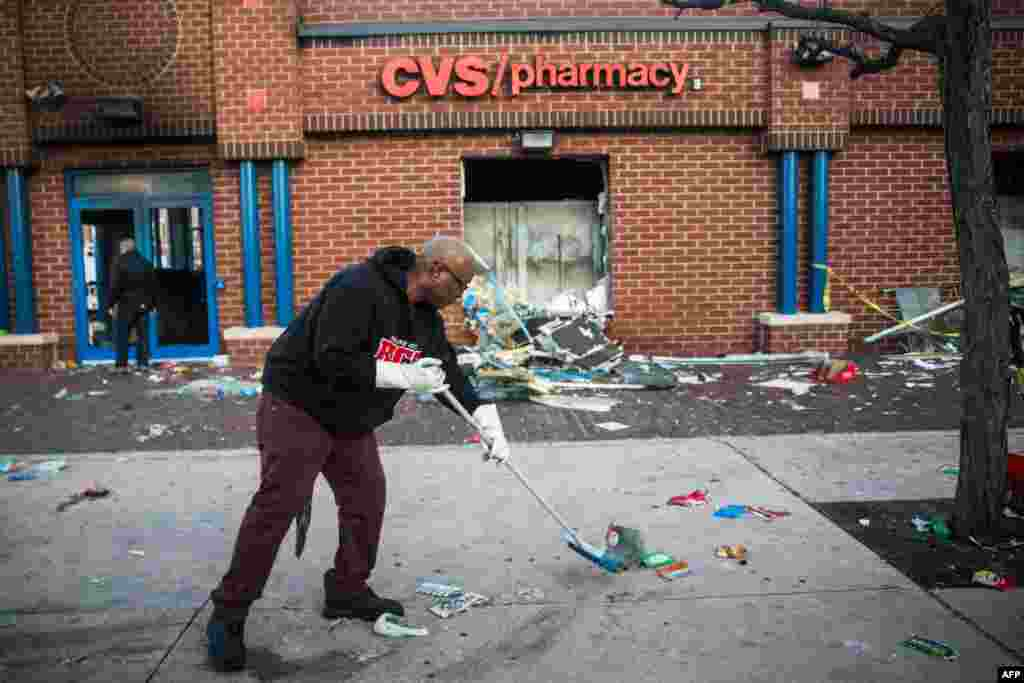 Jerald Miller helps clean up debris from a CVS pharmacy that was set on fire yesterday during rioting after the funeral of Freddie Gray, on April 28, 2015 in Baltimore, Maryland.