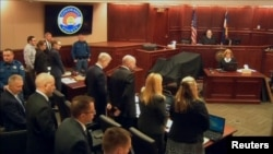 James Holmes (2nd L) stands at the start of his trial in Arapahoe County District Court in Centennial, Colorado in this still image captured from a pool video footage, April 27, 2015.