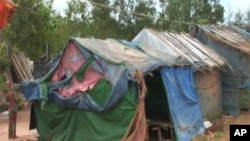 A Cambodian evictee stands by her hut in Preah Sihanouk Province. She is among 100 families that were evicted from a disputed land in April 2007.