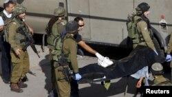 以色列军人抬着一具巴勒斯坦人的尸体,以色列警方说,这名巴勒斯坦人在持刀行凶后被击毙。(2015年10月29日)