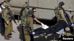 Tentara Israel mengangkat mayat warga Palestina yang ditembak polisi setelah menusuk petugas keamanan dengan pisau di Hebron, Tepi Barat (29/10).