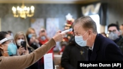 Gov. Ned Lamont has his temperature taken by Marie Cantara, left, at The Reservoir nursing facility, where the first COVID-19 vaccination was administered Friday, Dec. 18, 2020, in West Hartford, Conn