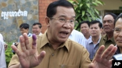 Cambodian Prime Minister Hun Sen gestures after casting his ballot in local elections at Ta Khmau town, in Kandal province, Sunday, June 3, 2012. Hun Sen's ruling party was expected to win the elections in a vote that monitors say is tainted by vote buyin