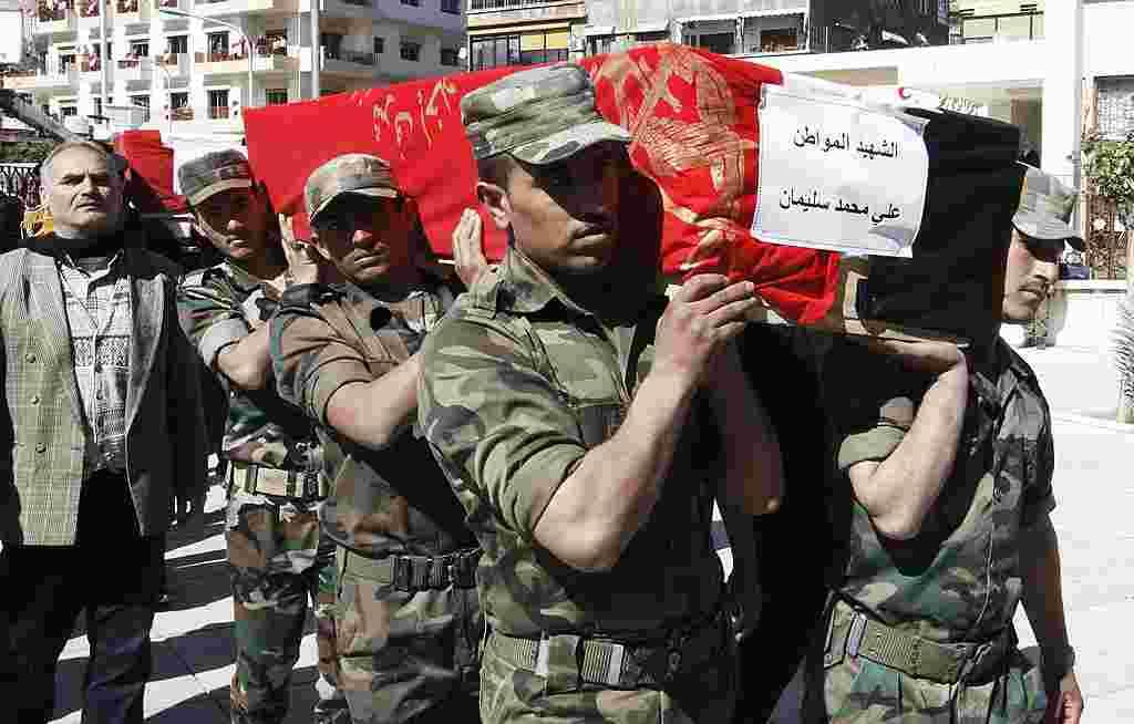 Militer Suriah membawa peti jenazah para korban pemboman di Damaskus, Suriah (AP).