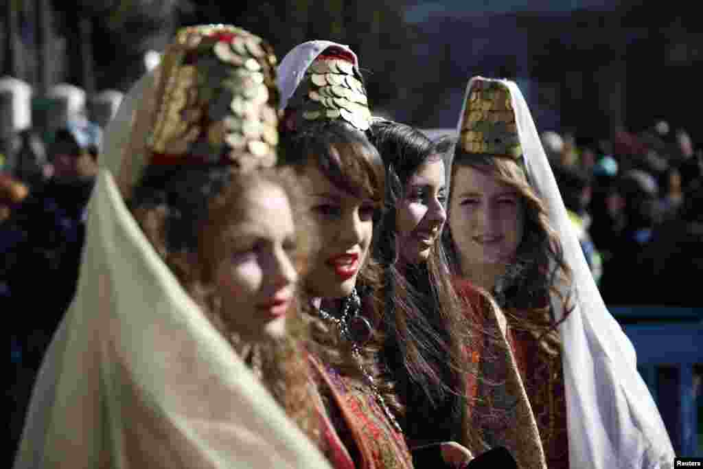 Girls wearing traditional Palestinian costumes take part in a Christmas procession at Manger Square in front of the Church of the Nativity in the West Bank town of Bethlehem, Dec. 24, 2013.