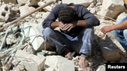 FILE - A man reacts on the rubble of damaged buildings after losing relatives to an airstrike in the besieged rebel-held al-Qaterji neighbourhood of Aleppo.