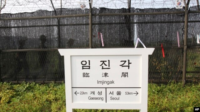 South Korean army soldiers patrol behind a barbed-wire fence near a directional sign showing the distance to North Korea's city Kaesong and South Korea's capital Seoul at the Imjingak Pavilion near the border village of Panmunjom, South Korea, July 5, 201