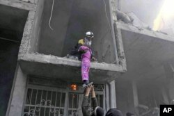 This photo released Feb. 21, 2018, provided by the Syrian Civil Defense group known as the White Helmets, shows a member of the Syrian Civil Defense group rescuing a young girl from a building damaged by airstrikes and shelling by Syrian government forces, in Ghouta, a suburb of Damascus, Syria.