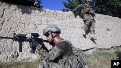US Army soldiers from Charlie company 4th platoon,1st brigade 3-21 infantry, jump over a wall during a patrol in the village of Chariagen in the Panjwai district of Kandahar province southern Afghanistan . President Barack Obama unveiled his plan to start