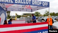 People drop off their mail in ballots from their vehicle as they vote in the U.S. presidential primary election in San Diego, California, United States, June 7, 2016.