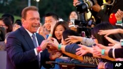 Actor and former Governor of California Arnold Schwarzenegger shakes hands with Chinese fans as he arrives for the grand opening of the 5th annual Beijing International Film Festival in Beijing, April 16, 2015.