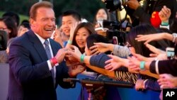 FILE - Actor and former Governor of California Arnold Schwarzenegger shakes hands with Chinese fans as he arrives for the grand opening of the 5th annual Beijing International Film Festival in Beijing, April 16, 2015.