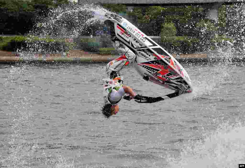A man flips his personal watercraft during a demonstration on the Sumida river in Tokyo, Japan.