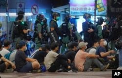 Police detain protesters during a march marking the anniversary of the Hong Kong handover from Britain to China, Wednesday, July. 1, 2020, in Hong Kong.