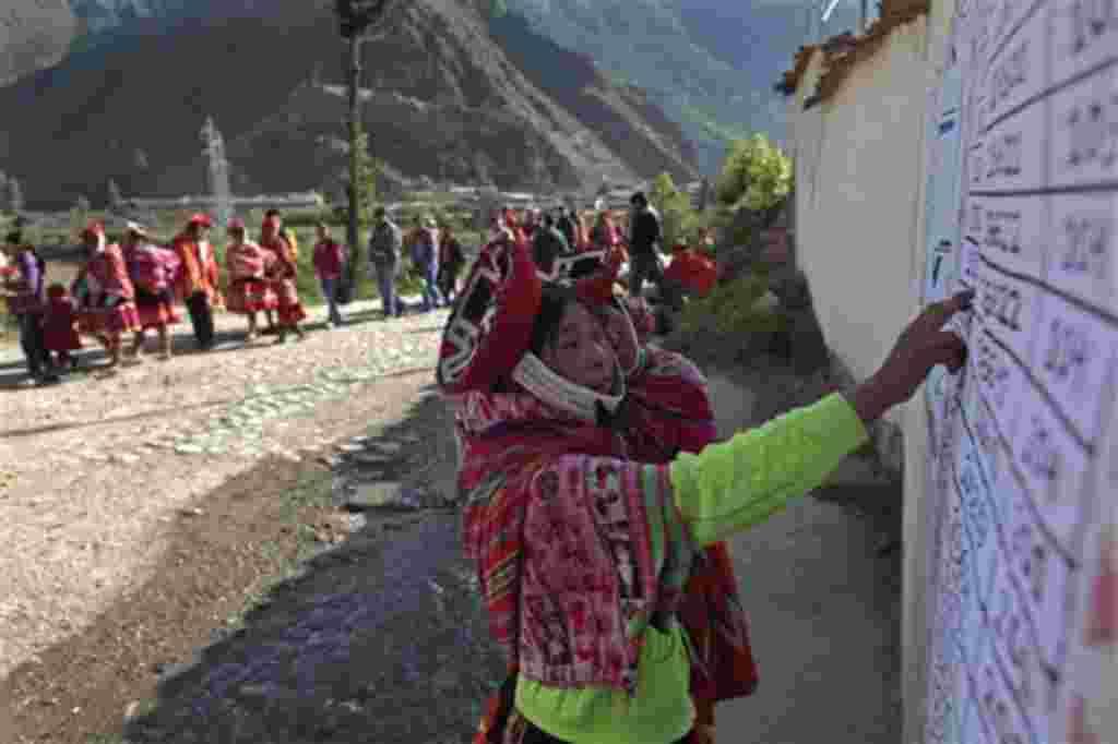 Dos mujeres indígenas buscan su registro en la mesa electoral para votar.