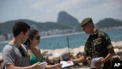 Một người lính phân phát những cuốn sách chứa những thông tin về muỗi Aedes aegypti tại các bãi biển ở Copacabana, Rio de Janeiro, 13/2/2016.