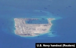 Chinese dredging vessels are purportedly seen in the waters around Fiery Cross Reef in the disputed Spratly Islands in the South China Sea in this still image from video taken by a P-8A Poseidon surveillance aircraft provided by the United States Navy.