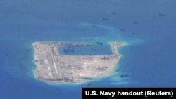 FILE - Chinese dredging vessels are purportedly seen in the waters around Fiery Cross Reef in the disputed Spratly Islands in the South China Sea in this still image from video taken by a P-8A Poseidon surveillance aircraft provided by the United States Navy.