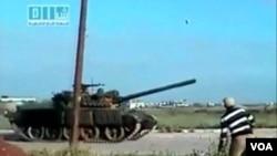Seorang pria melempar batu ke arah sebuah tank yang lewat di jalanan kota Dara'a, Senin (25/4).