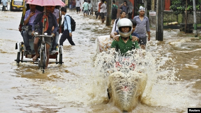 Commuters travel through a flooded street after heavy rains at Guwahati, in the northeastern Indian state of Assam, June 26, 2012.