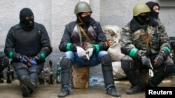 Pro-Russia armed men sit near police headquarters in Slovyansk April 13, 2014.
