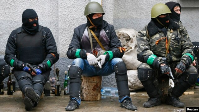 Pro-Russia armed men sit near police headquarters in Slovyansk April 13, 2014.