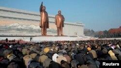 지난 2012년 12월 북한 김정일 사망 1주기를 맞아 평양 만수대 김일성, 김정일 동상을 찾은 주민들이 묵념을 하고 있다.