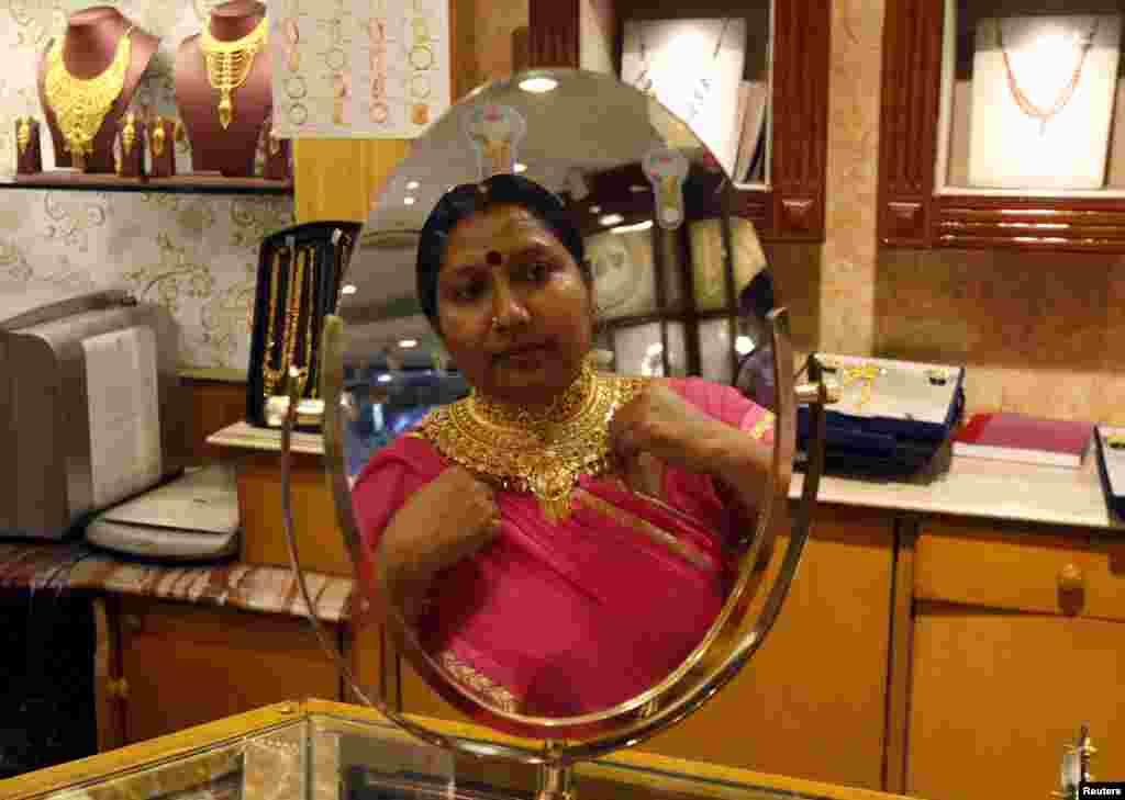 Seorang perempuan melihat bayangannya di cermin ketika sedang mencoba kalung di toko perhiasan di festival Akshaya Tritiya, festival beli emas besar di Kolkata, India.