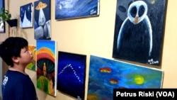 Lukisan Nur Agustinus terkait UFO. Kelompok BETA UFO Indonesia beranggotakan ribuan orang dari berbagai dunia saling berbagi info mengenai penampakan UFO. (Foto: VOA/Petrus Riski)