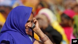 An Indian woman talks on her mobile phone at an election rally in Faizabad, India, Feb. 2, 2012.