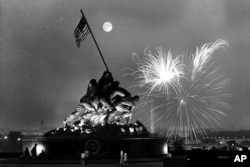 This view, from the Virginia side of the Potomac River, shows the moon above the Iwo Jima Statue as fireworks burst over Washington, D.C., on July 4, 1966.